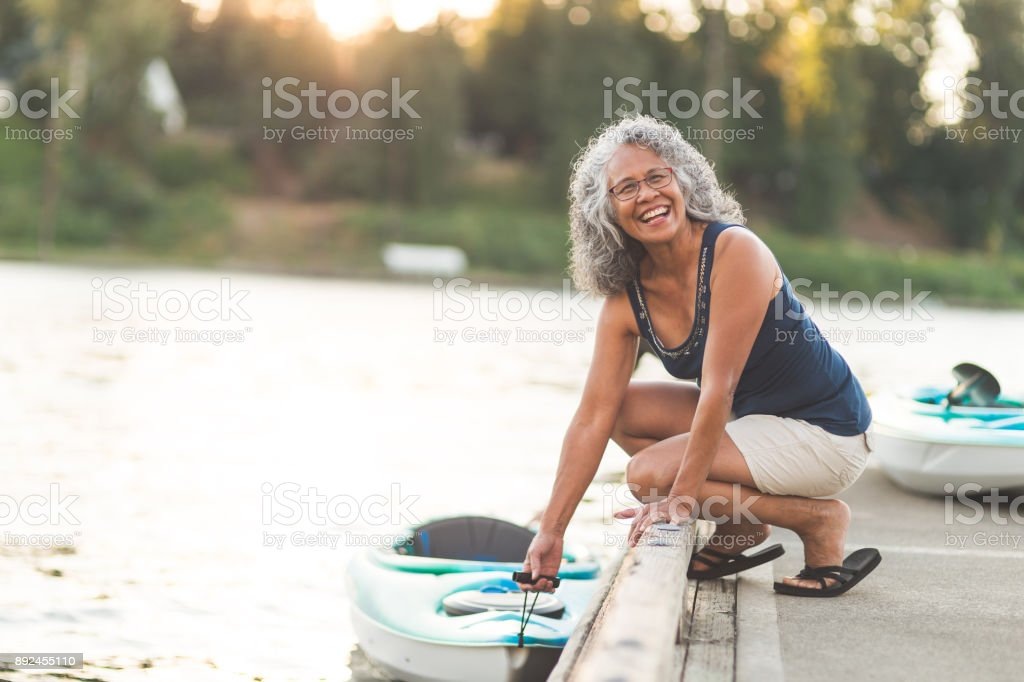 A beautiful ethnic older woman prepares to go kayaking stock photo