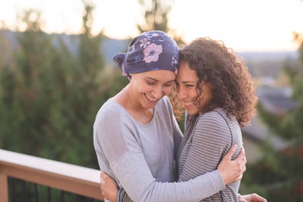 hermosa mujer étnica, luchando contra el cáncer abraza a su hermana bien - accesorio de cabeza fotografías e imágenes de stock