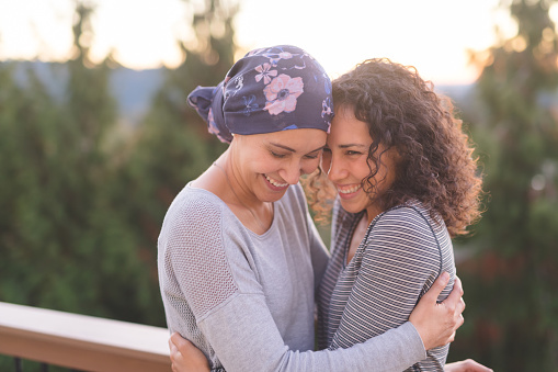 A beautiful young ethnic woman fighting cancer and wearing a head wrap embraces her sister. They are tightly holding each other and she is looking down and smiling. Her sister is also smiling. They are standing outdoors and there are mountains and trees in the background.