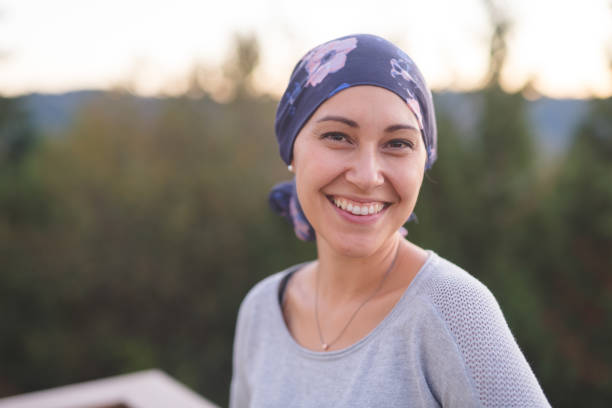 Beautiful Ethnic Woman with Cancer Smiles A beautiful young ethnic woman wearing a head wrap looks toward the camera and smiles radiantly. She is standing outdoors and there are mountains and trees in the background. headscarf stock pictures, royalty-free photos & images