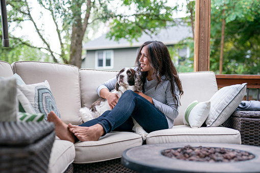 A gorgeous mixed race woman relaxing on patio furniture in her home's backyard while cuddling her pet dog. Pet adoption and emotional support mental health animal concepts.