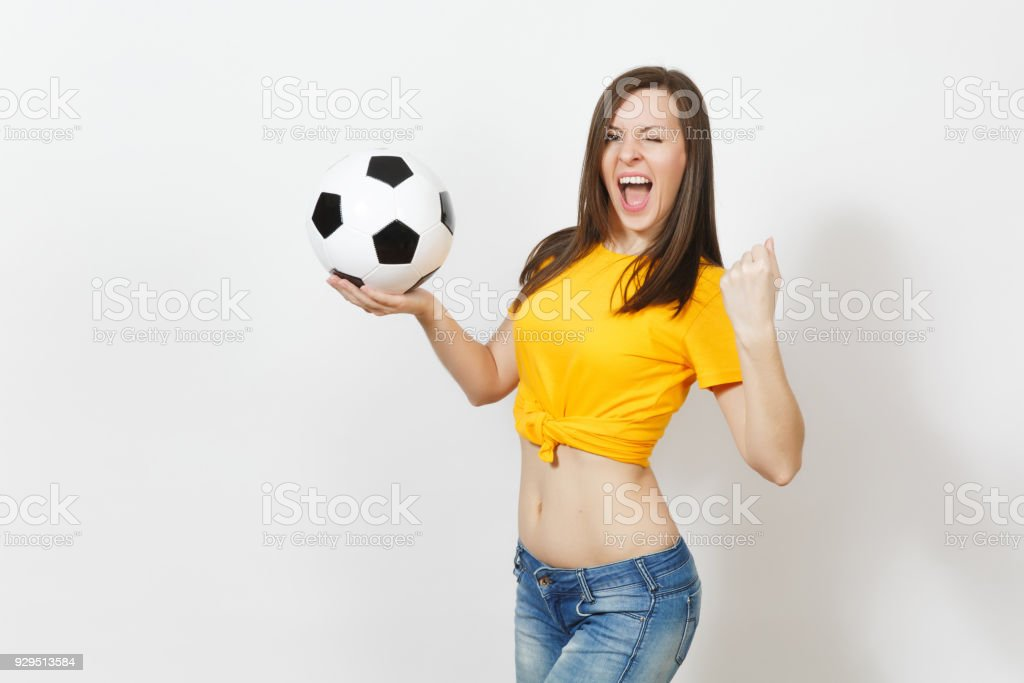 Beautiful European young strong slim sexy woman, football fan or player in yellow uniform holding soccer ball isolated on white background. Sport, play football, health, healthy lifestyle concept. stock photo