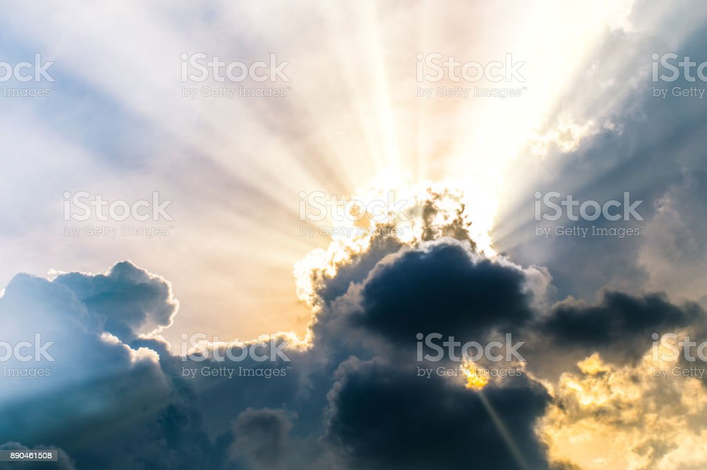 Beautiful evening skyscape. Sun's rays shine through hole in black clouds after rain. Sky, Golden sky. Natural background. Inspirational concept. stock photo