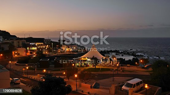 Porto Moniz, Madeira, Portugal - 10-30-2017: Beautiful evening view over illuminated village after sunset with famous natural swimming pools on the shore of Atlantic Ocean.