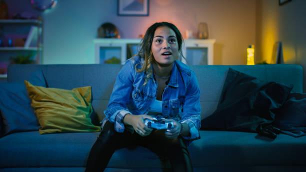 mooie opgewonden jonge zwarte gamer meisje zittend op een bank en het spelen van video games op een console. ze speelt met een draadloze controller. knusse kamer is verlicht met warm en neon licht. - gaming stockfoto's en -beelden