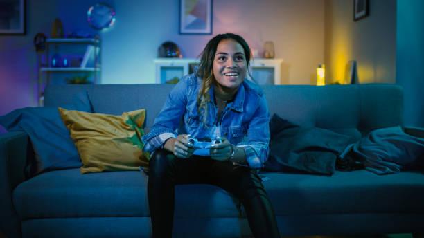 Schöne aufgeregt junge schwarze Gamer Mädchen sitzt auf einer Couch und spielen Videospiele auf einer Konsole. Sie spielt mit einem Wireless Controller. Das Cozy Room ist mit warmem und Neonlicht im Licht. – Foto