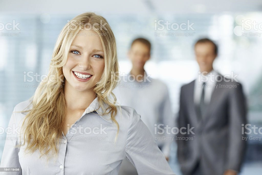 Beautiful executive smiling with colleagues in the background royalty-free stock photo