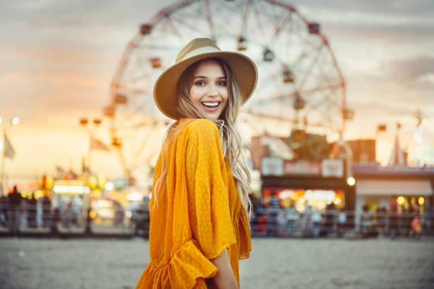 Beautiful exited smiling tourist woman having fun at amusement park stock photo