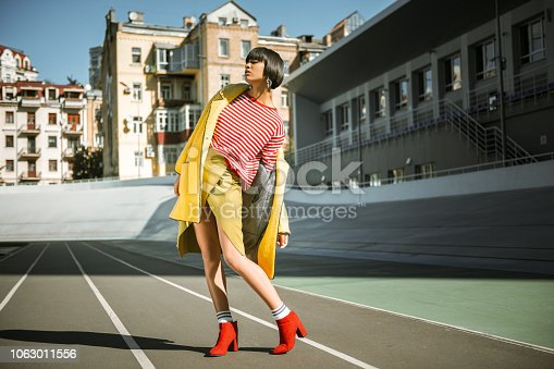 Attractive awkward girl. Beautiful extraordinary girl lady wearing geometrical dusty yellow skirt having houses on the background