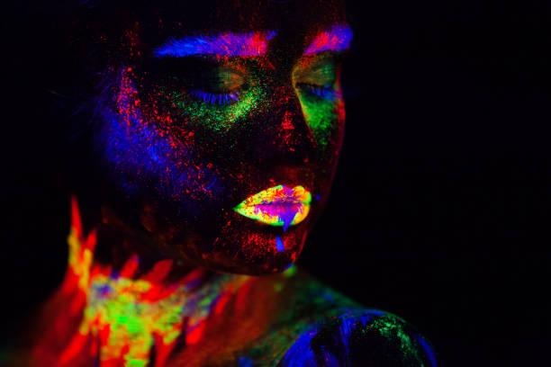 schöne außerirdischen modell frau im neonlicht. es ist portrait schöne modell mit fluoreszierenden make-up, künstlerischer entwurf der weiblichen posiert im uv mit bunten make up. auf schwarzem hintergrund isoliert - tanz make up stock-fotos und bilder