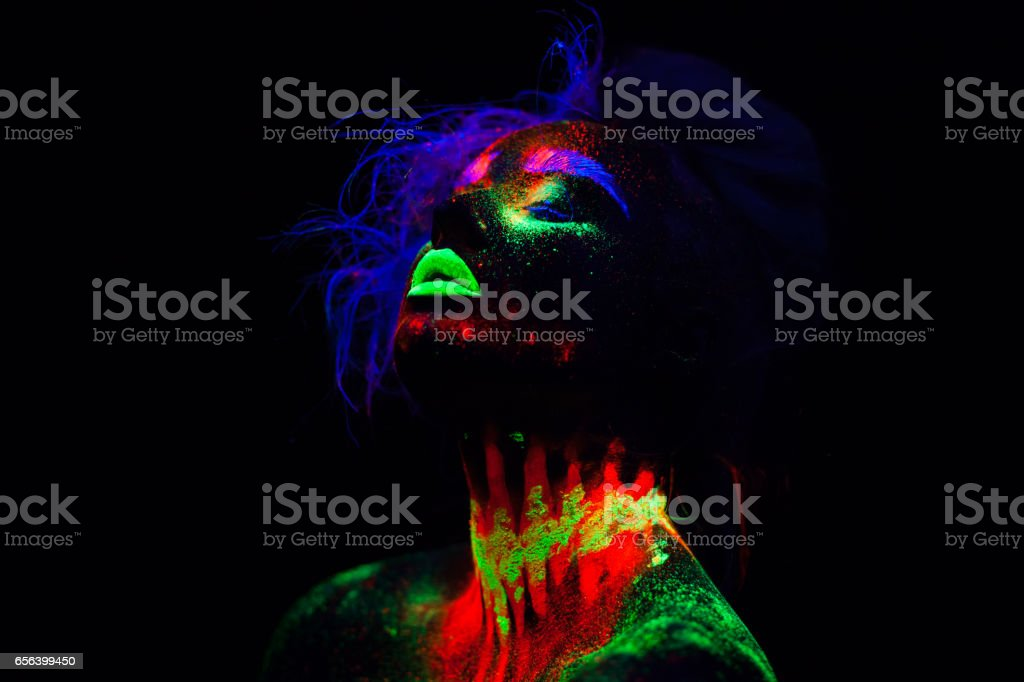Beautiful extraterrestrial model woman with blue hair and green lips in neon light. It is portrait of beautiful model with fluorescent make-up, Art design of female posing in UV with colorful make up. Isolated on black background stock photo