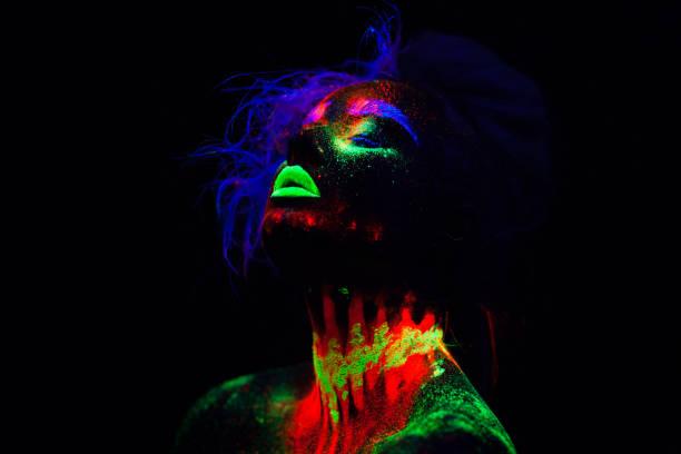 schöne außerirdischen modell frau mit blauen haaren und grünen lippen im neonlicht. es ist portrait schöne modell mit fluoreszierenden make-up, künstlerischer entwurf der weiblichen posiert im uv mit bunten make up. auf schwarzem hintergrund isoliert - fluoreszierend stock-fotos und bilder