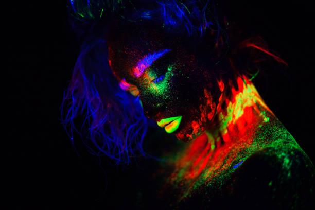 schöne außerirdischen modell frau mit blauen heair und grünen lippen im neonlicht. es ist portrait schöne modell mit fluoreszierenden make-up, künstlerischer entwurf der weiblichen posiert im uv mit bunten make up. auf schwarzem hintergrund isoliert - tanz make up stock-fotos und bilder