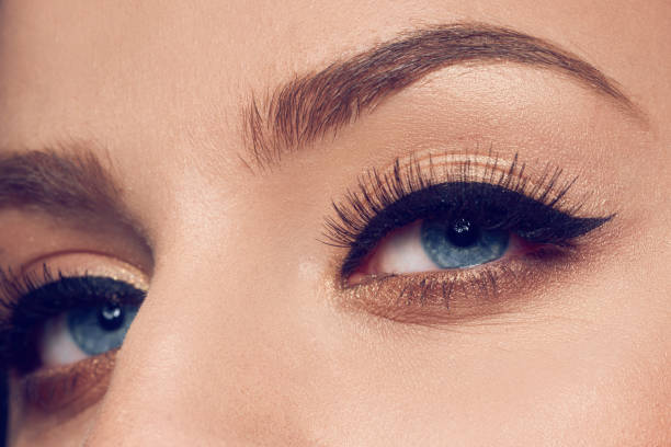 beautiful eyes with makeup macro shot of woman with blue eyes and false eyelashes looking at camera. false eyelash stock pictures, royalty-free photos & images