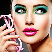 Beautiful Face of a woman with green vivid make-up of eyes and pink glasses.