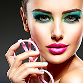 Beautiful Face of a woman with green vivid make-up of eyes and hold pink glasses.