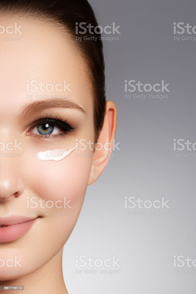 Beautiful face of young woman with cosmetic cream on a cheek. Sk – Foto