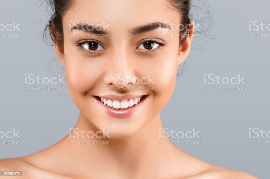 Beautiful Face of young woman with perfect skin. Gray background