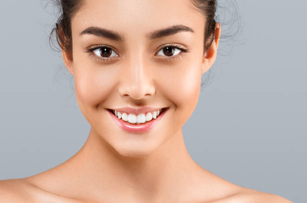 beautiful face of young woman with perfect skin. gray background - clear sky stock pictures, royalty-free photos & images