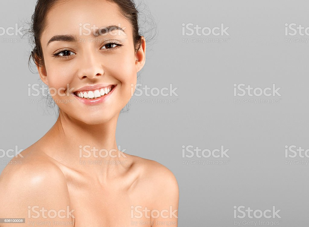 Beautiful Face of young woman with perfect skin. Gray background stock photo