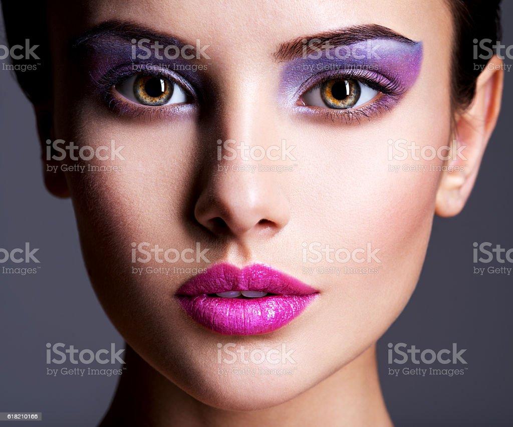 Beautiful face with purple eye make-up stock photo