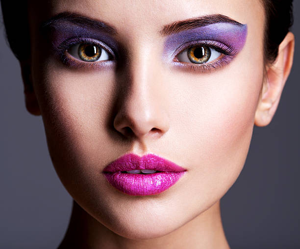 Beautiful face with purple eye make-up The girl's face closeup with purple eye make-up. fashion makeup. Studio stage make up stock pictures, royalty-free photos & images