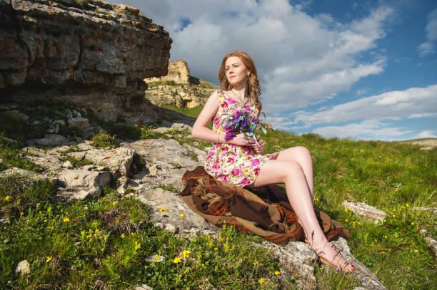 schöne blondes mädchen sitzt auf tartan plaid auf der klippe mit einem blumenstrauß in händen - hochzeitsfrisur boho stock-fotos und bilder