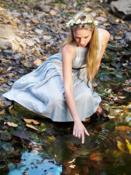 wunderschöne märchen prinzessin sitzung von wasser-teich und zehenspitzen reflexion - teichfiguren stock-fotos und bilder