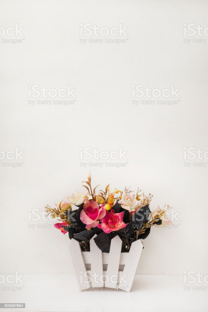 Beautiful fake and colorful dried flowers in rustic pot on white...