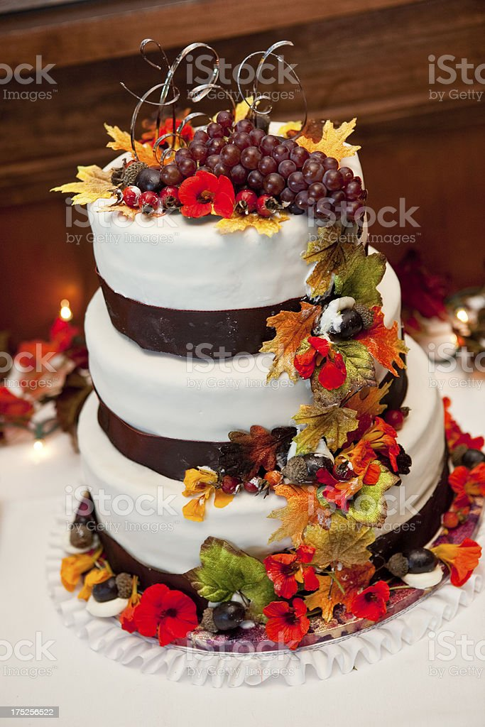 Beautiful Fall Wedding Cake with Grapes, Autumn Leaves, and Acorns stock photo