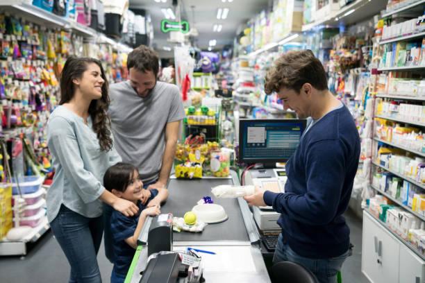 Belle famille à une animalerie checking out et acheter beaucoup de produits pour leur chien et le sympathique vendeur leur inscription dans le système - Photo