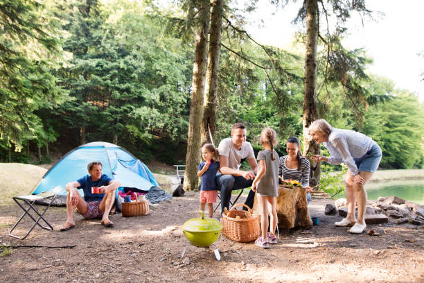 beautiful family camping in forest, eating together. - camping stock photos and pictures