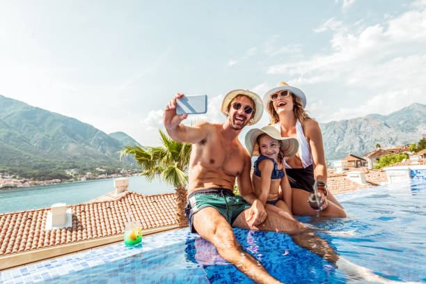 beautiful family enjoying summer day by  the pool, making selfie stock photo
