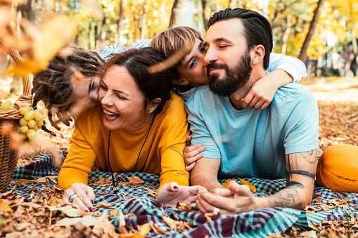 Beautiful family having fun on an autumn picnic in park, lying on a picnic carpet