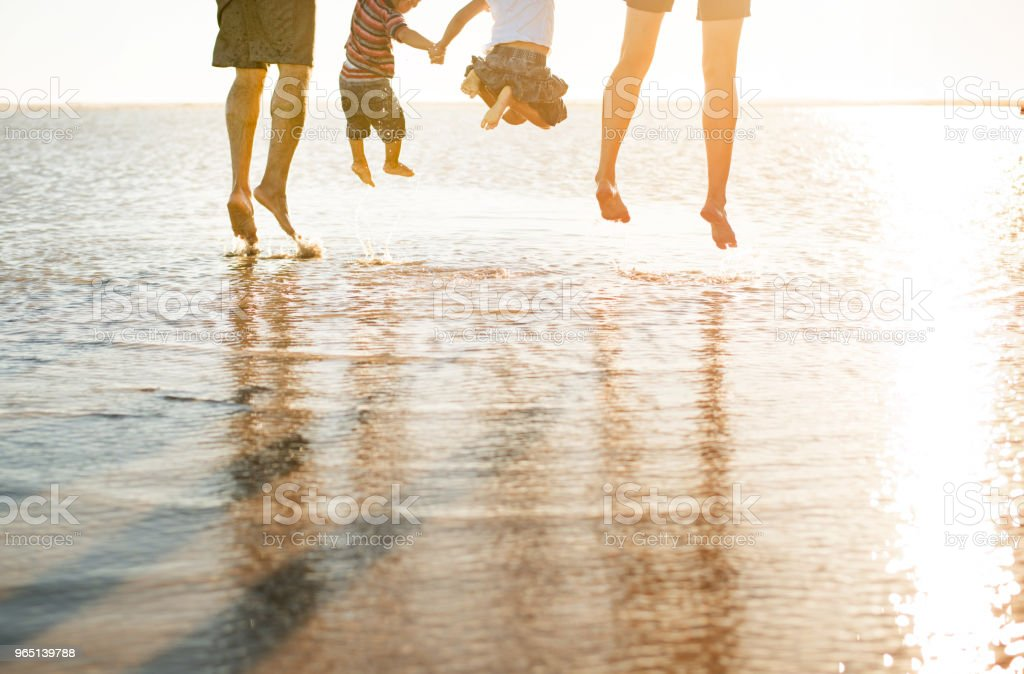 Beautiful family holding hands jumping and playing in the ocean royalty-free stock photo