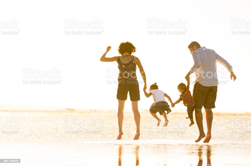 Beautiful family holding hands jumping and playing in the ocean zbiór zdjęć royalty-free