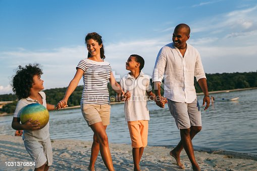 Beautiful family holding hands walking on the beach