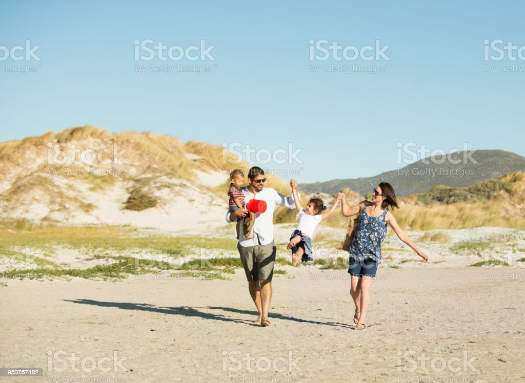 Beautiful family holding hands walking on the beach stock photo