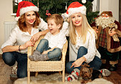 Beautiful family of mother, daughter and son sitting on the sofa near Christmas tree. A Yorkshire terrier lying nearby.