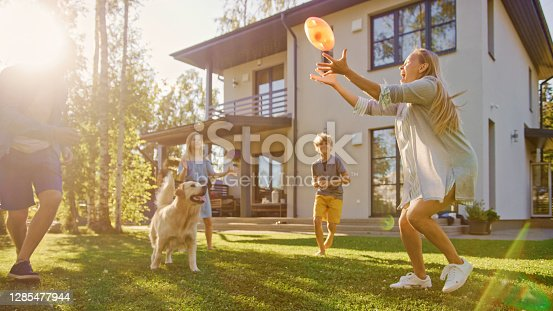 istock Beautiful Family of Four Play Catch Toy Ball with Happy Golden Retriever Dog on the Backyard Lawn. Idyllic Family Has Fun with Loyal Pedigree Dog Outdoors in Summer House Backyard. 1285477944