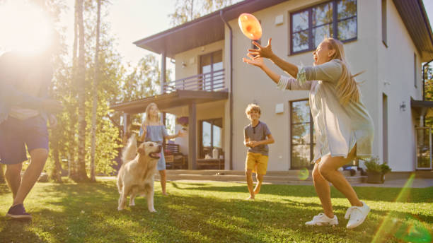 Beautiful Family of Four Play Catch Toy Ball with Happy Golden Retriever Dog on the Backyard Lawn. Idyllic Family Has Fun with Loyal Pedigree Dog Outdoors in Summer House Backyard. stock photo