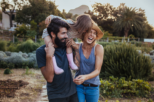 Beard man carrying little girl on shoulder with woman laughing at the farm. Beautiful family of three having fun at their farm.