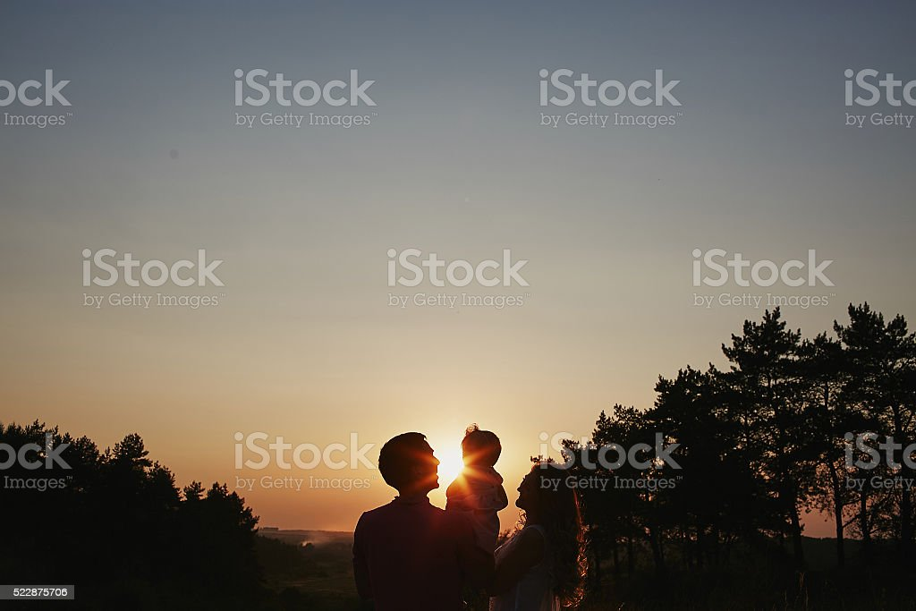 beautiful family of three people, mom dad and daughter stock photo