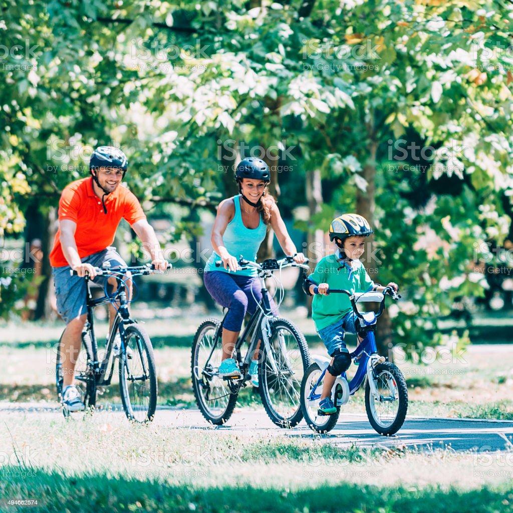 Beautiful family riding bicycles stock photo