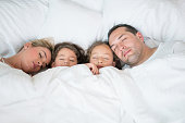 Beautiful Latin American family sleeping together in bed