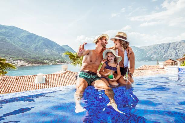 Beautiful family take selfie in a swimming pool stock photo