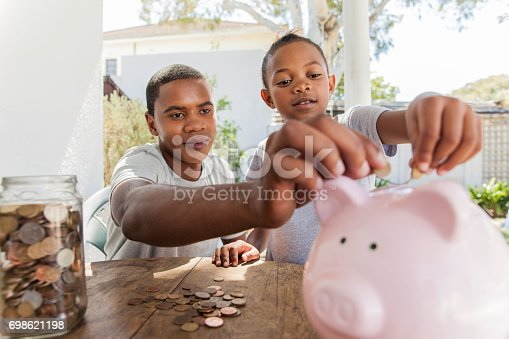 African father throwing coins into a piggy bank with his daughter.