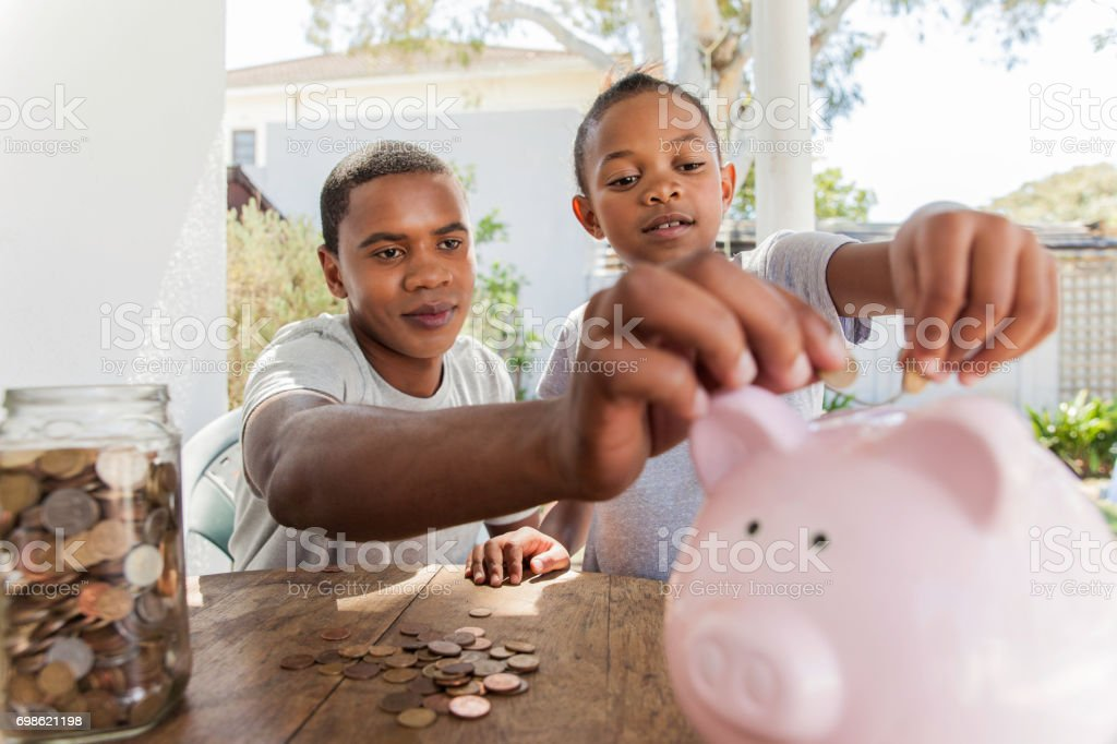 Beautiful family throwing coins into a piggy bank together. stock photo