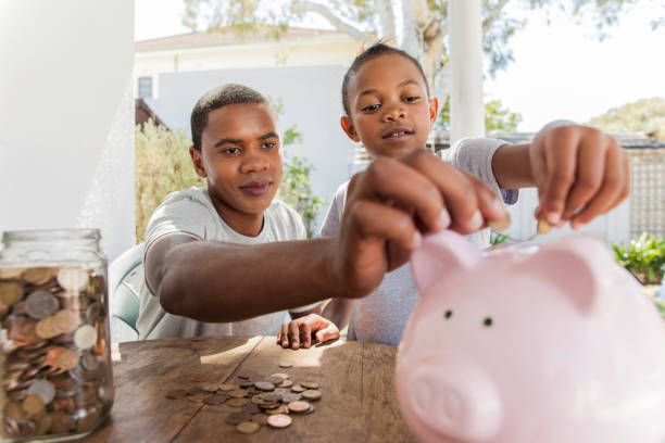 Beautiful family throwing coins into a piggy bank together. African father throwing coins into a piggy bank with his daughter. allowance stock pictures, royalty-free photos & images