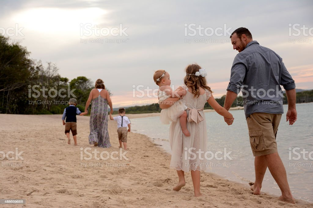 Beautiful Family walking along the beach together stock photo